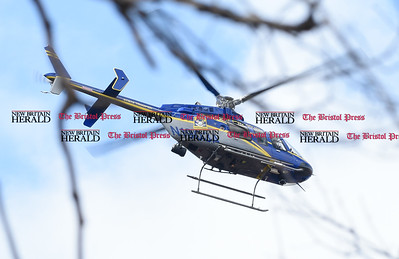 033017  Wesley Bunnell | Staff  A CT State Police helicopter hovers overhead in the woods off of Loon Lake Rd in Plainville searching for missing hiker Arthur Williams who was last seen Saturday.