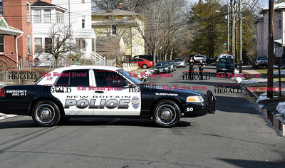 032917  Wesley Bunnell | Staff  New Britain Police stand outside of a home on Olive St in New Britain as part of an investigation into an earlier shooting of three people on Newington Ave on Wednesday morning.