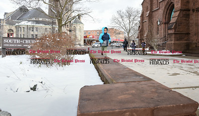 031017  Wesley Bunnell | Staff  Ten year old Jaiden Johnson runs along a low wall outside of South Church in downtown New Britain on Friday March 10 with some snow still visible from the morning snow storm.