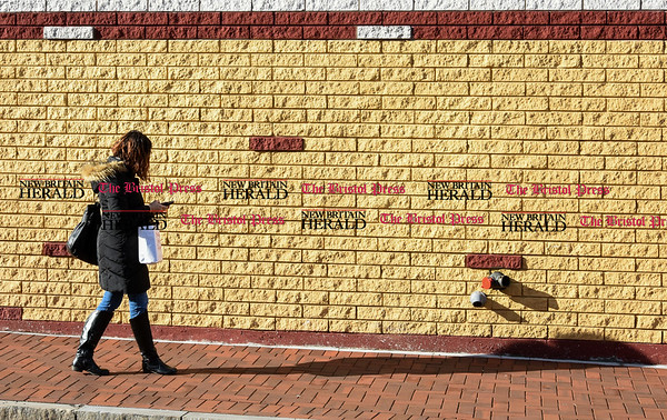 030917 Wesley Bunnell   Staff Angelis Almenas walks down Walnut St New Britain in the late day sun on Friday March 10.