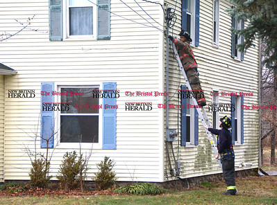 3/1/2017 Mike Orazzi | Staff Bristol firefighters reattach a cable line to a home on Lewis Street during a windy Wednesday afternoon.