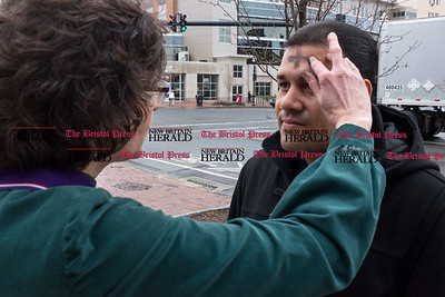 030117  Wesley Bunnell | Staff  Pastor Jane Rowe stood outside South Church on Ash Wednesday as part of Ashes to Go. The service is about bringing the service out from behind church doors and into places of everyday life. Pastor Rowe rubs ashes into the cross shape onto Rafael Guzman Jr.