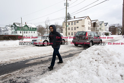 031517  Wesley Bunnell | Staff  A resident is forced to walk in the road on on East St on Wednesday March 15. Many sidewalks remained snow covered the day after the blizzard while roads also remained difficult to drive.