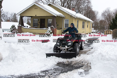 031517  Wesley Bunnell | Staff  Adding a snow plow to his ATV Pedro Rosado makes short work of snow piled up in his driveway on Wed March 15.