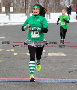 Brittany Heninger, of Bristol, crosses the finish line of the two mile course of the Shamrock Run in Bristol, Mar. 18, 2017. With a time of 10:38, Heninger was the top female finisher for the two mile run. (Photo by Christopher Zajac)