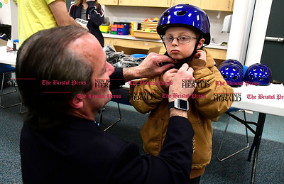 3/25/2017 Mike Orazzi | Staff Bristol Elks Club Exalted Ruler Shawn Martin adjusts a new bike helmet worn by J.J. Redway during the Children's Department the annual safety fair Saturday. Members of the Bristol Elks Lodge 1010 distributed close to 100 helmets to area children for the 9th year.