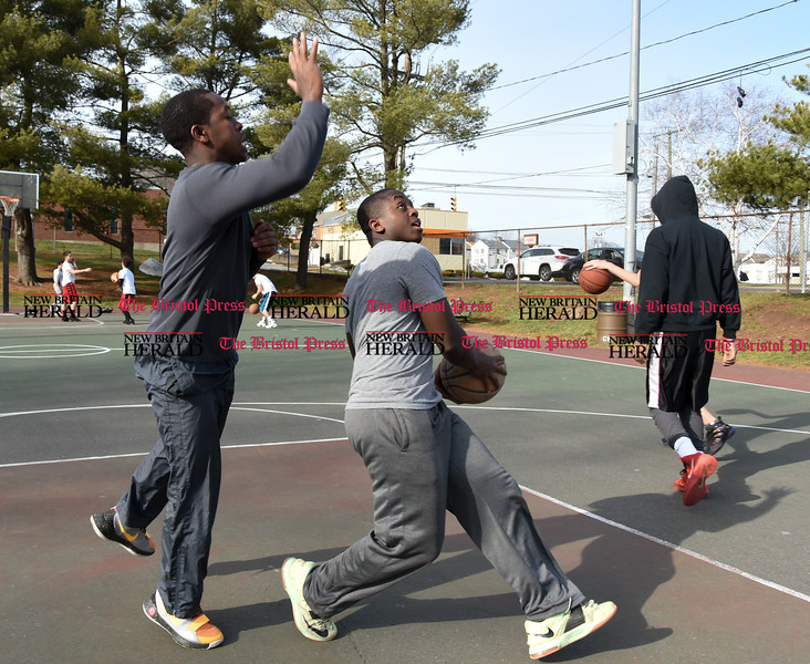 033017  Wesley Bunnell | Staff<br /> <br /> Brothers Kizito, left, & Moise Moket play basketball at Chesley Park on a mild Thursday afternoon.