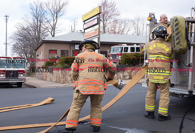 030317  Wesley Bunnell | Staff  New Britain Firefighters pack up equipment after putting out a fire at the Big Daddy 2 Laundromat at 145 Stanley St on Friday March 3.