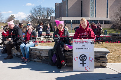 030817  Wesley Bunnell | Staff  A rally was held on CCSU's campus in solidarity with the International Women's Strike at noon on Wed March 8. Director Emeritus of the Women's Center Doris Honig Guenter, left, sits with Professor of Astonomy Kristine Larsen holding a sign of support for the rally. Participants chose to wear red and hats in a further show of solidarity.