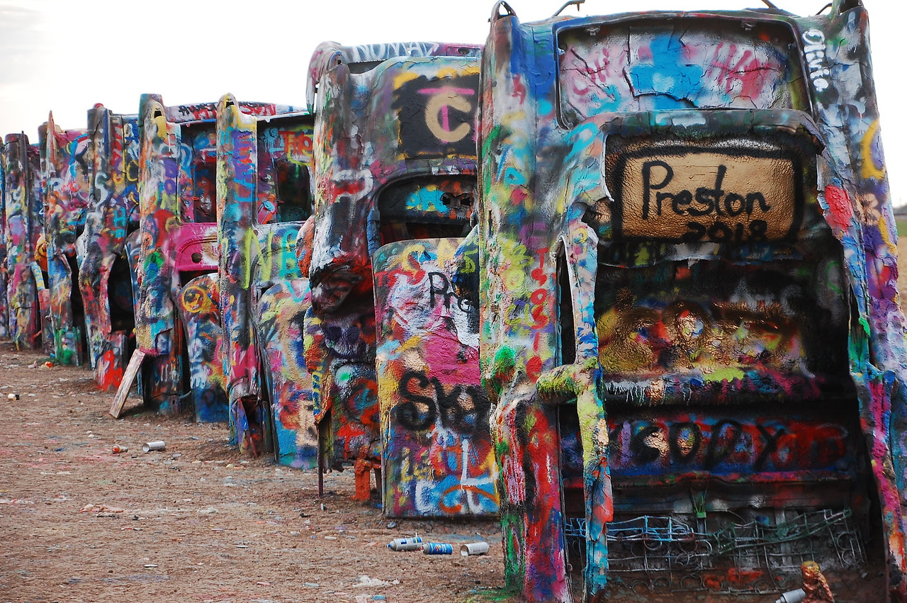 Cadillac Ranch.  The thing to do is to spray paint the old cars.  It's allowed - hell, it's encouraged.  When you are done with the can, you just chuck it on the ground.