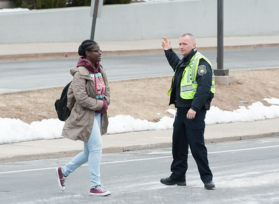03/21/18  Wesley Bunnell | Staff  New Britain High School Resource Officer Jerzy Chmura stops traffic for a student leaving Wednesday on early dismissal due to the nor'easter expected later in the day.