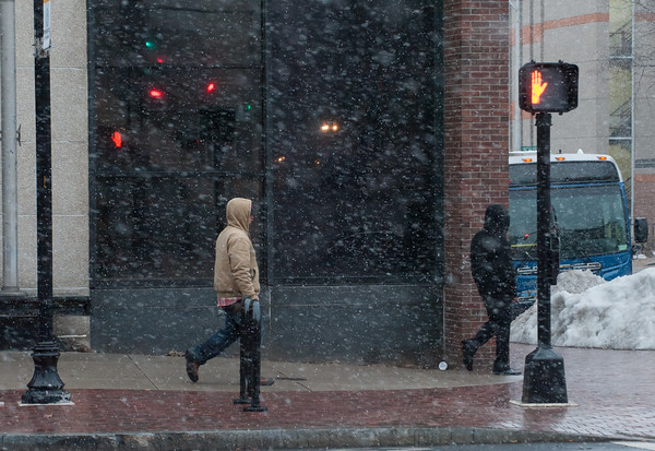 03/21/18 Wesley Bunnell | Staff CT Transit passengers make their way down Main Street towards the buses during the beginning of snow flurries on Wednesday evening. The expected nor'easter started late in the day after many businesses and schools closed early for the day.