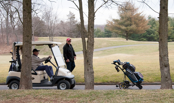 03/29/18 Wesley Bunnell | Staff Donald Seifel drives a golf cart as friend Ed Rosario walks along side controlling his battery powered golf cart at Stanley Golf Course on opening day Thursday morning.
