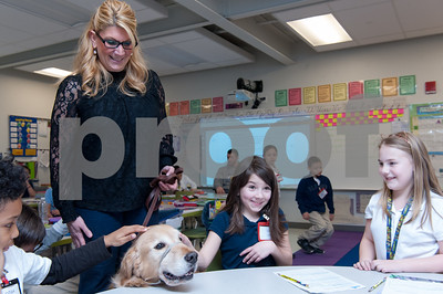 03/02/18  Wesley Bunnell | Staff  Gaffney Elementary School Principal Anita Fazio stands with her dog Cooper who is trained as a therapy dog as she visits Ms. Libby's third grade class on Friday for Dr. Seuss Day aka Read Across America Day.  Petting Cooper is Lily Diabrowski as Jemma Hapgood looks on.