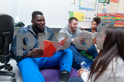 03/02/18  Wesley Bunnell | Staff  CCSU student and football player Cheickna Douceur reads to Genesis Lopez in Ms. Libby's third grade class on Dr. Seuss Day aka Read Across America Day at Gaffney Elementary School on Friday as fellow football player Mike Mushaw reads alongside.