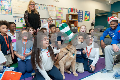 03/02/18  Wesley Bunnell | Staff  Genesis Lopez, L, and Ethan Rodriguez, R, keep a steady hand on therapy dog Cooper on Friday during Dr. Seuss Day aka Read Across America Day. The students are part of Ms. Libby's third grade class while Cooper is also the personal dog of Principal Anita Fazio, standing.  CCSU football player Tymir Hinton who is part of a volunteer group of student athletes looks on.