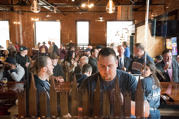 03/30/18 Wesley Bunnell | Staff 5 Churches Brewing held their ribbon cutting with city officials on Friday at noon to a crowd of customers lined down the sidewalk. Jake Lounsbury pours a beer for customer as the packed crowd can be seen in the background.