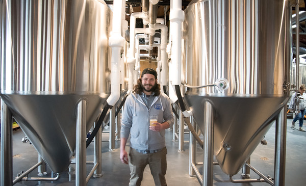 03/30/18 Wesley Bunnell | Staff 5 Churches Brewing held their ribbon cutting with city officials on Friday at noon to a crowd of customers lined down the sidewalk. Brewer Austin Japs stops to pose for a photo in the brew room.