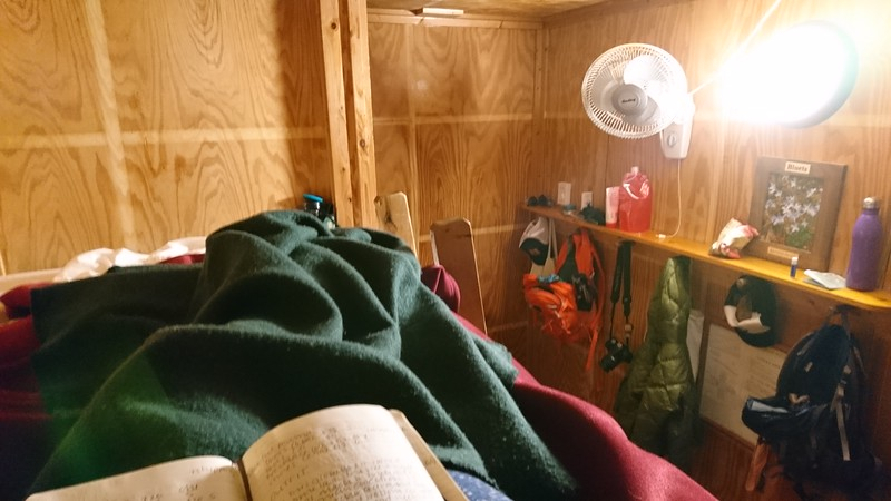 The photo shows legs covered in blankets and a room with hooks holding jackets and backpacks