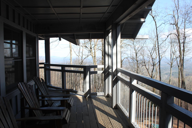 Two Adirondack chairs sit on a porch overlooking the mountains