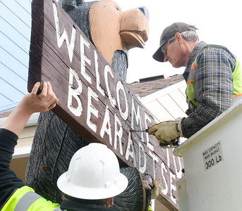 "Mike Houdek screws the ""Welcome To Bearadise"" sign back onto the Black Bear Diner bear sculpture Thursday after it was set in its new location at the Paradise Police Department in Paradise. (Matt Bates -- Enterprise-Record)"