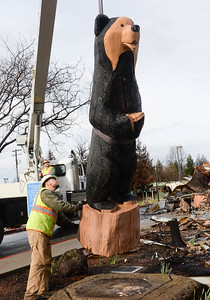 Corey Martin works the crane controls and Adam Payne guides the Black Bear Diner bear sculpture as they move the wooden sculpture off its base Thursday in Paradise. (Matt Bates -- Enterprise-Record)