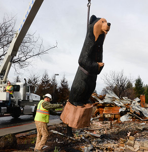 Corey Martin, left, works the crane as Adam Payne controls the swaying while they lift the Black Bear Diner bear sculpture off its base Thursday in Paradise. (Matt Bates -- Enterprise-Record)