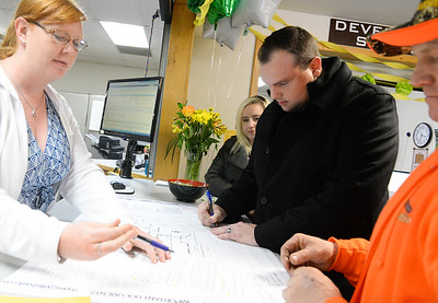 Anne Vierra, left, shows Jason Buzzard(center) and his contractor Jon Hornback, right, where to sign their permit paperwoork as Meagann Buzzard watches at Paradise Town Hall on Thursday, March 28. (Matt Bates -- Enterprise-Record)
