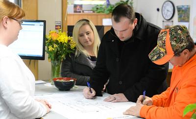 Jason Buzzard, center, and his contractor Jon Hornback, right, sign their permit paperwork as Meagann Buzzard(left) watches at Paradise Town Hall on Thursday, March 28. (Matt Bates -- Enterprise-Record)