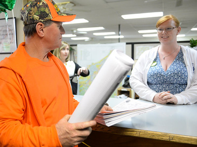 Contractor Jon Hornback gets blueprints for the Buzzards' new house from Anne Vierra at Paradise Town Hall on Thursday, March 28. (Matt Bates -- Enterprise-Record)