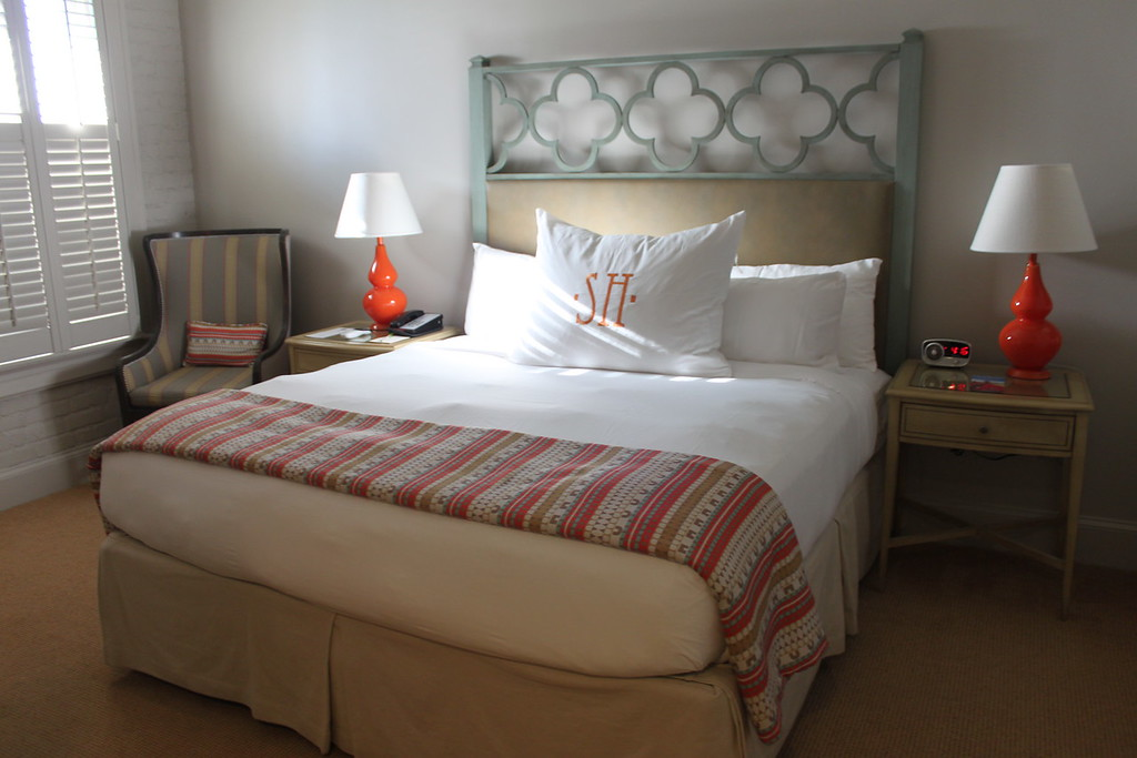 The Southern Hotel decorative headboard with white sheets and orange lamps