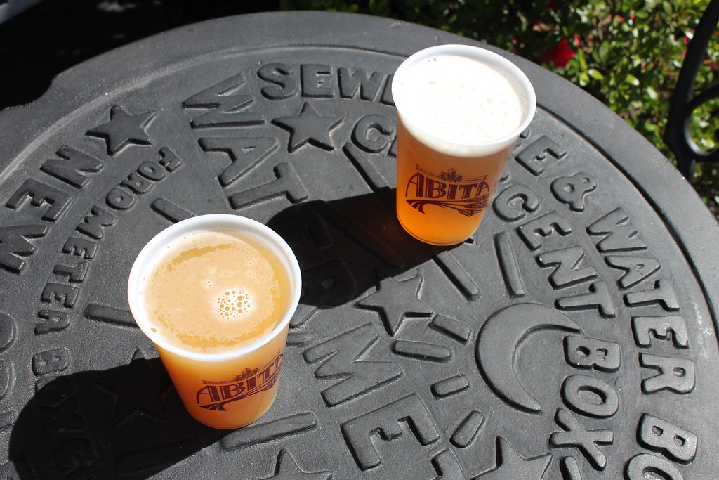 Abita Brewery two plastic cups of beer on an iron table with the design of New Orleans sewer grates