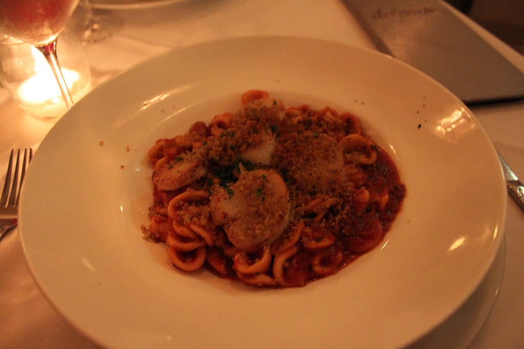 Del Porto white plate of pasta with orichette and scallops topped in red sauce and breadcrumbs