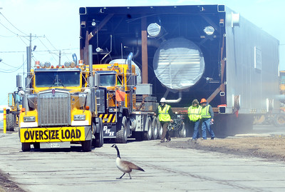 WARREN DILLAWAY / Star Beacon A GOOSE wanders in front of heavy equipment hauling a 200 foot long portion of a compressor being towed to Middle Road on Monday afternoon in Ashtabula. The trucks are pulling from the entrance to Kinder Morgan Pinney Dock where the compresssor from Italy was prepared for the journey.