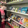 KEVIN HARVISON |<br /> Parker Intermediate School student Hope Wilbur looks over a book during the Scholastic Book Fair that continues to Friday.