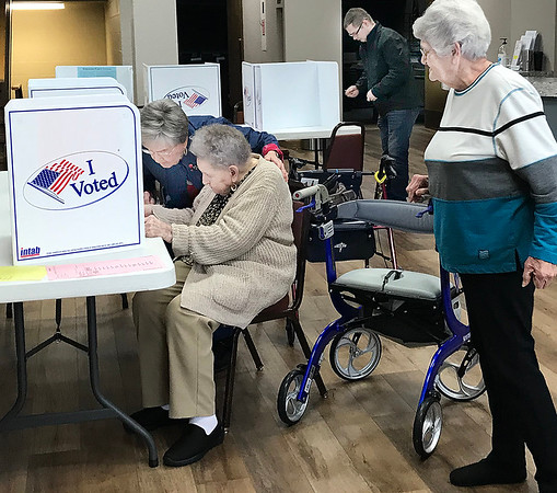 KEVIN HARVISON |<br /> Helen Peters, Precinct 3 Inspector, right, watches as Margie Gattenby, center, gets some assistance casting her vote Tuesday.