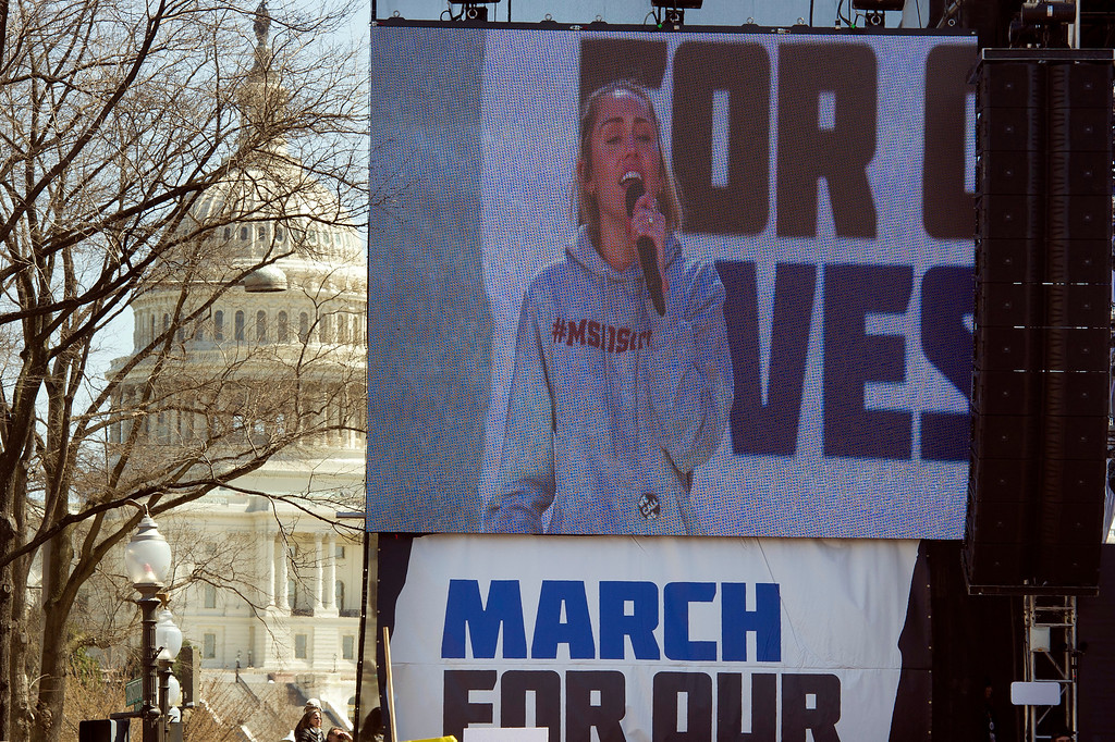 """. With the U.S. Capitol behind the stage, Miley Cyrus is seen on a video screen while she performs at the \""""March for Our Lives\"""" rally in support of gun control in Washington, Saturday, March 24, 2018, on Pennsylvania Avenue near the U.S. Capitol, in Washington. (AP Photo/Cliff Owen)"""