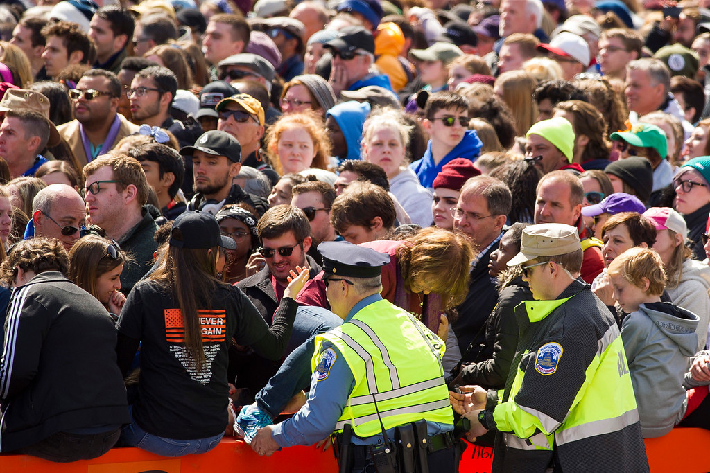""". Metropolitan Police officers help a woman leave a crowded secure area at the \""""March for Our Lives\"""" rally in support of gun control in Washington, Saturday, March 24, 2018, on Pennsylvania Avenue near the U.S. Capitol. (AP Photo/Cliff Owen)"""