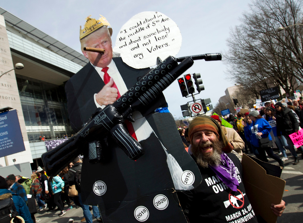 ". A protester holds up a sign during the ""March for Our Lives\"" rally in support of gun control in Washington, Saturday, March 24, 2018, on Pennsylvania Avenue near the U.S. Capitol. (AP Photo/Jose Luis Magana)"