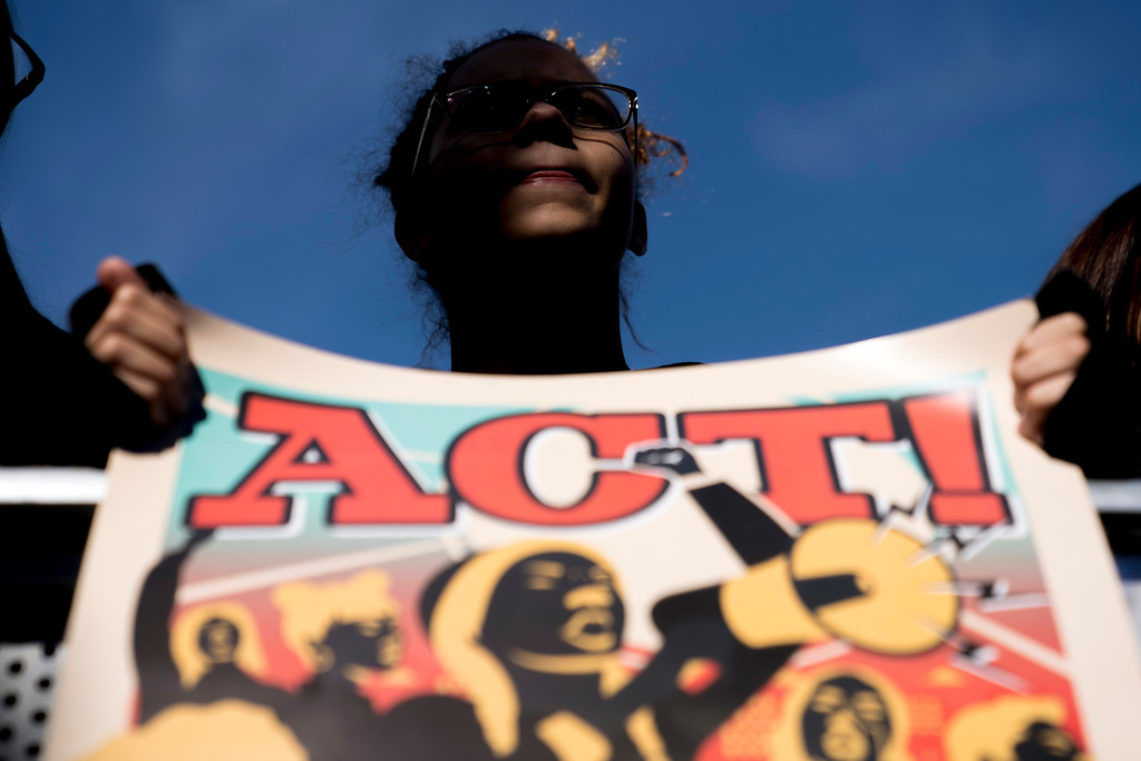 ". A student from Marjory Stoneman Douglas High School holds a sign during the ""March for Our Lives\"" rally in support of gun control in Washington, Saturday, March 24, 2018. (AP Photo/Andrew Harnik)"