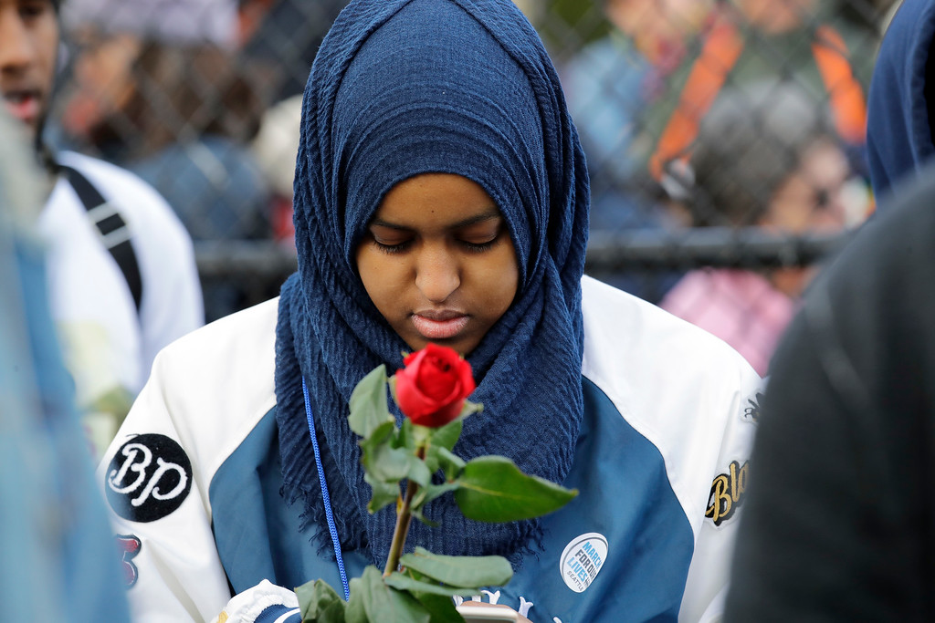 . Naj Ali, a high school senior, holds a rose in memory of a person lost to gun violence during a rally before a march in favor of gun control Saturday, March 24, 2018, in Seattle.   Summoned to action by student survivors from Marjory Stoneman Douglas High School in Parkland, Fla., hundreds of thousands of teenagers and their supporters rallied in the nation\'s capital and cities across the U.S. on Saturday to press for gun control. (AP Photo/Elaine Thompson)