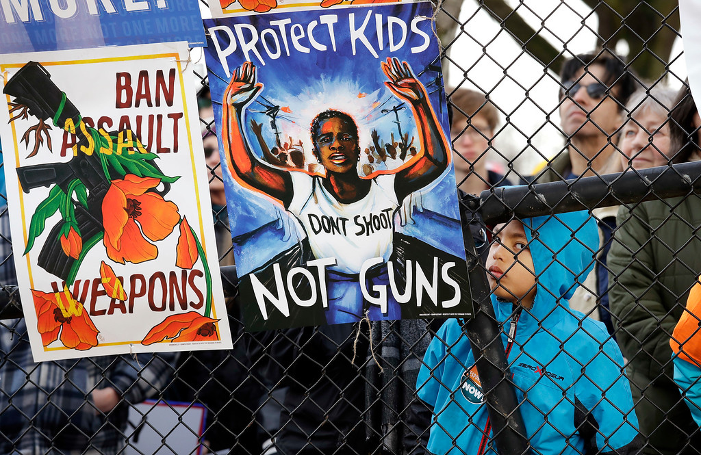 . Kai Stolworthy, 7, looks on from behind a fence during a rally before a march in favor of gun control Saturday, March 24, 2018, in Seattle.  Summoned to action by student survivors from Marjory Stoneman Douglas High School in Parkland, Fla., hundreds of thousands of teenagers and their supporters rallied in the nation\'s capital and cities across the U.S. on Saturday to press for gun control. (AP Photo/Elaine Thompson)