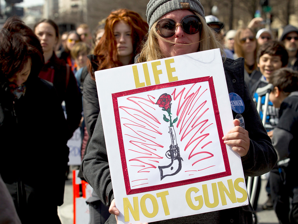 """. Jody Becker holds up a sign during a moment of silence at the \""""March for Our Lives\"""" rally in support of gun control in Washington, Saturday, March 24, 2018, on Pennsylvania Avenue near the U.S. Capitol. (AP Photo/Jose Luis Magana)"""