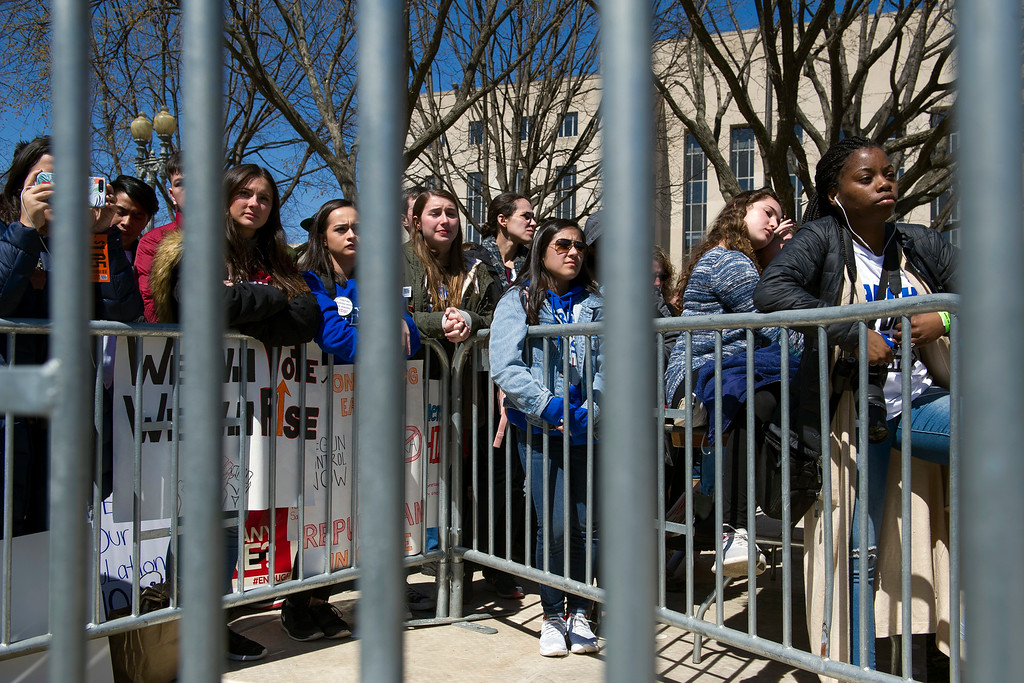 """. Protesters stand behind security fencing as they attend the \""""March for Our Lives\"""" rally in support of gun control in Washington, Saturday, March 24, 2018, on Pennsylvania Avenue near the U.S. Capitol, in Washington. (AP Photo/Cliff Owen)"""