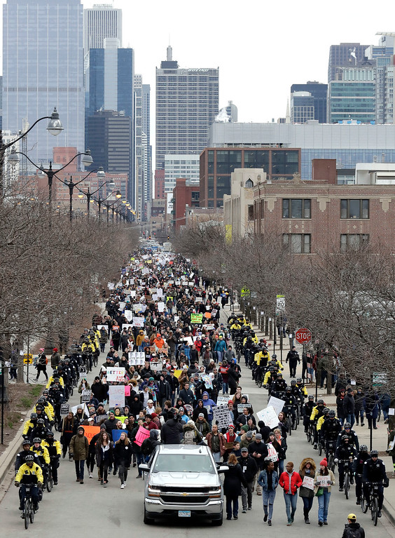 """. Demonstrators Demonstrators walk through on the West Randolph street during a \""""March for Our Lives\"""" rally in support of gun control, Saturday, March 24, 2018, in Chicago. Students and activists across the country planned events Saturday in conjunction with a Washington march spearheaded by teens from Marjory Stoneman Douglas High School in Parkland, Fla., where over a dozen people were killed in February. (AP Photo/Nam Y. Huh)"""