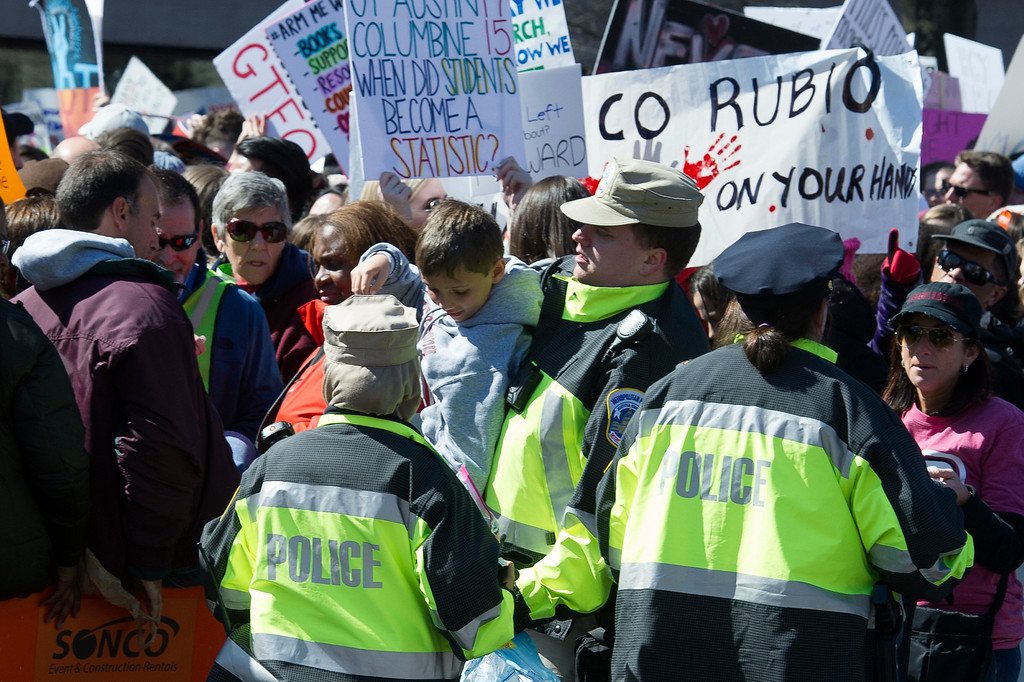 ". Metropolitan Police officers help a young boy across a security barrier from a crowded area at the ""March for Our Lives\"" rally in support of gun control in Washington, Saturday, March 24, 2018, on Pennsylvania Avenue near the U.S. Capitol. in Washington. (AP Photo/Cliff Owen)"