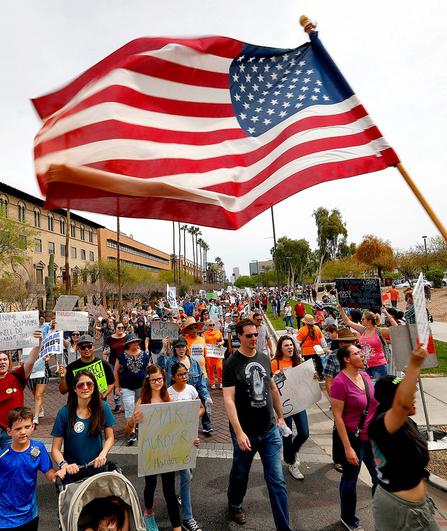 """. People participate in the \""""March For Our Lives\"""" rally at the Capitol Saturday, March 24, 2018, in Phoenix. The nationwide student-led protest is demanding stricter gun laws in the wake of the Feb. 14 shooting that killed 17 in Parkland, Fla.  (AP Photo/Matt York)"""