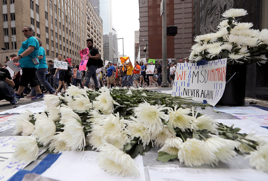 ". Demonstrators pass a makeshift memorial to school shooting victims during a ""March for Our Lives\"" protest for gun legislation and school safety Saturday, March 24, 2018, in Houston. Students and activists across the country planned events Saturday in conjunction with a Washington march spearheaded by teens from Marjory Stoneman Douglas High School in Parkland, Fla., where 17 people were killed in February. (AP Photo/David J. Phillip)"