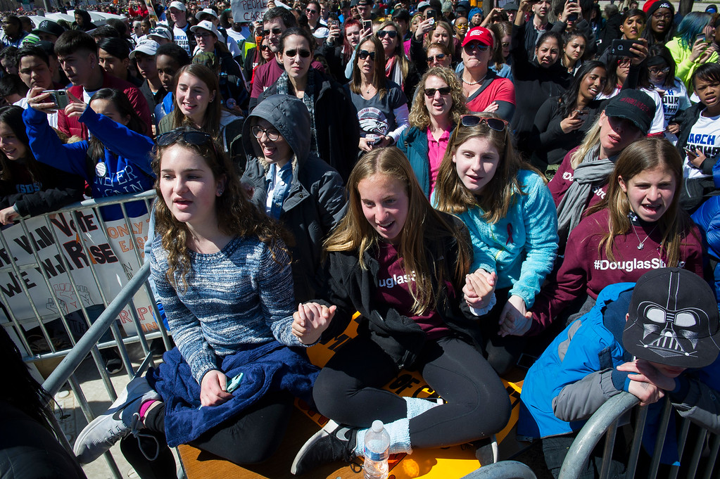 """. Protestors sing-along with Miley Cyrus during the \""""March for Our Lives\"""" rally in support of gun control in Washington, Saturday, March 24, 2018, on Pennsylvania Avenue near the U.S. Capitol, in Washington. (AP Photo/Cliff Owen)"""