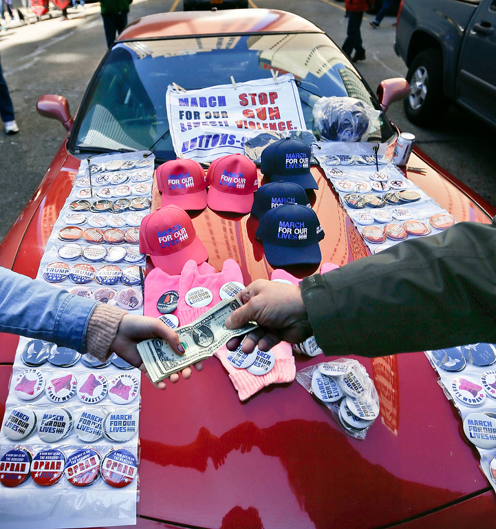 ". A vendor sells one of his hats promoting the ""March for Our Lives\"" from the hood of his car near the crowd gathering for the march in support of gun control, Saturday, March 24, 2018, in Pittsburgh. (AP Photo/Keith Srakocic)"